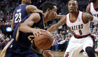 New Orleans Pelicans guard Brian Roberts, left, drives on Portland Trail Blazers guard Damian Lillard during the first half of an NBA basketball game in Portland, Ore., Sunday, April 6, 2014. (AP Photo/Don Ryan)