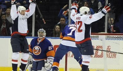 New York Islanders goalie Evgeni Nabokov (20) watches Washington Capitals' Jason Chimera (25) and Joel Ward (42) celebrate Ward's goal in the second period of an NHL hockey game on Saturday, April 5, 2014, in Uniondale, N.Y. The Capitals won 4-3 in a shoot out. (AP Photo/Kathy Kmonicek)