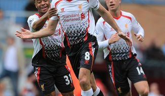 Liverpool's Steven Gerrard (centre) celebrates after scoring his team's opening goal during their English Premier League match against West Ham at Upton Park, London,  Sunday, April 6, 2014.   (AP Photo / Nick Potts,PA)  UNITED KINGDOM OUT  NO SALES  NO ARCHIVE