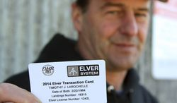 In this photo made Friday, April 4, 2014, fisherman Tim LaRochelle displays his new electronic swipe card for elver fishing in Portland, Maine, that permits him to catch elvers during the 2014 elver fishing season. Maine now requires its fishermen use the cards to record sales of the baby eels in its second most valuable fishing business, after lobstering. (AP Photo/Blake Davis)