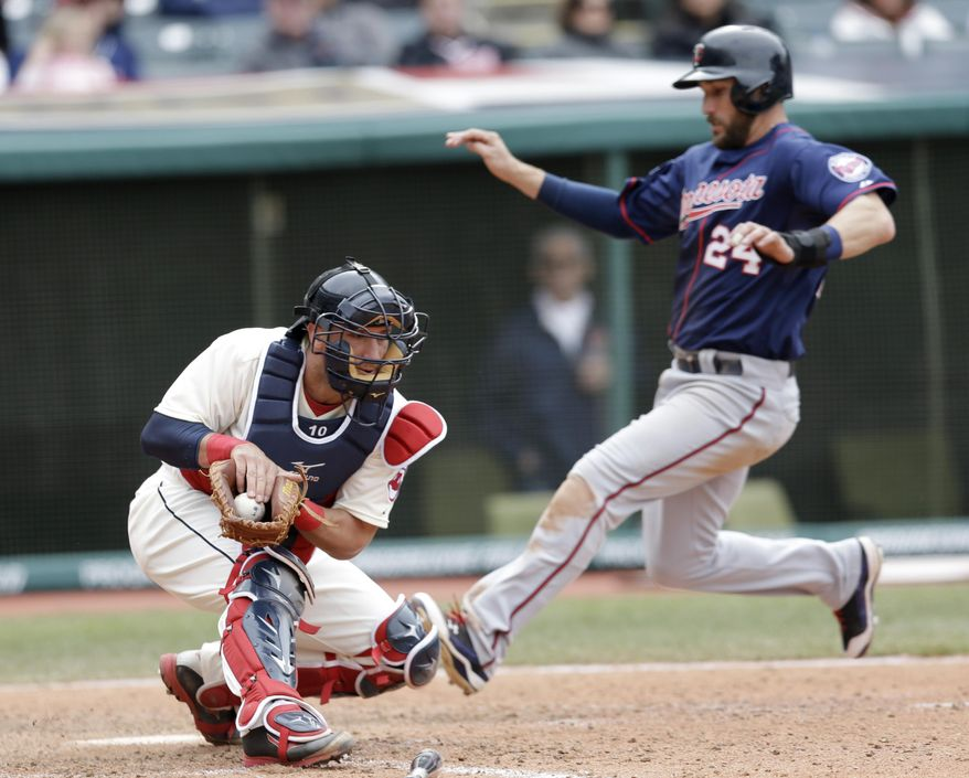 Cleveland Indians' Yan Gomes, left, gets the ball but can't make the tag as Minnesota Twins' Trevor Plouffe (24) scores on Aaron Hicks sacrifice fly in the ninth inning of an MLB American League baseball game, Sunday, April 6, 2014, in Cleveland. The Twins defeated the Indians 10-7. (AP Photo/Tony Dejak)