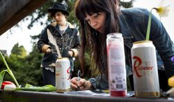 "Portland residents Ashly Archibald, 26, left, and Kim Hoffman, 28, right, scrawls the quote, ""who needs action when you have words?"" in memory of Nirvana's lead singer, Kurt Cobain, on a bench near the home where he died on the 20th anniversary of his death Saturday, April 5, 2014, at Viretta Park in Seattle, Wash. On April 10, Nirvana will be inducted into the Rock and Roll Hall of Fame. (AP Photo/seattlepi.com, Jordan Stead) STAND ALONE PHOTO. MAGS OUT; NO SALES; SEATTLE TIMES OUT; MANDATORY CREDIT; TV OUT"