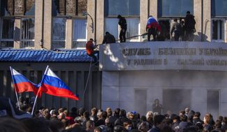 Pro-Russian activists with Russian national flags storm the Ukrainian regional office of the Security Service in Luhansk, Ukraine, Sunday, April 6, 2014. In Luhansk, 30 kilometers (20 miles) west of the Russian border, hundreds of people surrounded the local headquarters of the security service and later scaled the facade to plant a Russian flag on the roof.  (AP Photo/Igor Golovniov)