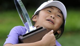 """Kelly Xu, Girls 7-9 overall category winner, holds her trophy after the """"Drive, Chip and Putt"""" contest at Augusta National on Sunday, April 6, 2014, in Augusta, Ga. (AP Photo/The Augusta Chronicle, Rainier Ehrhardt)"""