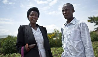In this photo taken Wednesday, March 26, 2014, Emmanuel Ndayisaba, right, and Alice Mukarurinda, pose for a photograph outside Alice's house in Nyamata, Rwanda. She lost her baby daughter and her right hand to a manic killing spree. He wielded the machete that took both. Yet today, despite coming from opposite sides of an unspeakable shared past, Alice Mukarurinda and Emmanuel Ndayisaba are friends. She is the treasurer and he the vice president of a group that builds simple brick houses for genocide survivors. They live near each other and shop at the same market. Their story of ethnic violence, extreme guilt and, to some degree, reconciliation is the story of Rwanda today, 20 years after its Hutu majority killed more than 1 million Tutsis and moderate Hutus. The Rwandan government is still accused by human rights groups of holding an iron grip on power, stifling dissent and killing political opponents. But even critics give President Paul Kagame credit for leading the country toward a peace that seemed all but impossible two decades ago. (AP Photo/Ben Curtis)