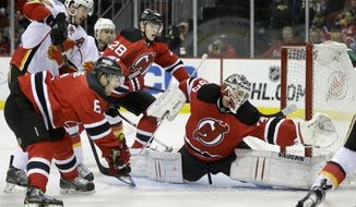 New Jersey Devils goalie Cory Schneider (35) stretches to protect the net as Calgary Flames Curtis Glencross, left, presses between Devil's ' Andy Greene (6) and Anton Volchenkov (28), of Russia, during the first period of an NHL hockey game in Newark, N.J., Monday, April 7, 2014. (AP Photo/Mel Evans)