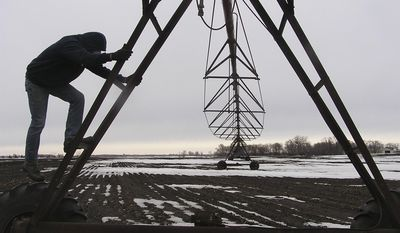 Farmer Jim Anderson climbs one of his many irrigation rigs near Brooten, Minn. in an undated photo. As irrigation booms in Minnesota, hundreds of farmers appear to be pumping groundwater for their crops without the required state permits.  (AP Photo/Minnesota Public Radio, Mark Steil)