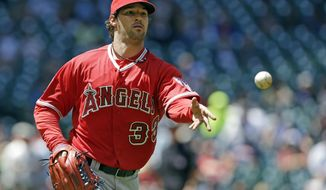 Los Angeles Angels starting pitcher C.J. Wilson throws to first base for the out on Houston Astros' Robbie Grossman in the first inning of a baseball game Monday, April 7, 2014, in Houston. (AP Photo/Pat Sullivan)