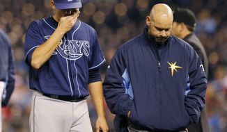 Tampa Bay Rays starting pitcher Matt Moore, left, walks off the field with a trainer following an injury during the sixth inning of the MLB American League baseball game against the Kansas City Royals at Kauffman Stadium in Kansas City, Mo., Monday, April 7, 2014. (AP Photo/Orlin Wagner)