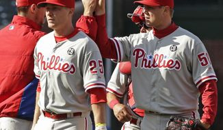 Philadelphia Phillies closer Jonathan Papelbon (58), right, celebrates with starter Cliff Lee after the Phillies defeated the Chicago Cubs 2-0 in a baseball game in Chicago, Saturday, April 5, 2014. (AP Photo/Nam Y. Huh)