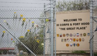 Flowers decorate a fence outside of Fort Hood's east gate on Sunday, April 6, 2014, in Killeen, Texas, in honor of those killed and wounded in the Fort Hood shooting on April 2. Three people were killed and 16 were wounded when a gunman opened fire before taking his own life at the Fort Hood military base. (AP Photo/ Tamir Kalifa)