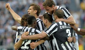 Juventus forward Fernando Llorente, of Spain,  top left, celebrates after scoring with teammates during a Serie A soccer match between Juventus and Livorno at the Juventus stadium, in Turin, Italy, Monday, April 7, 2014. (AP Photo/Massimo Pinca)