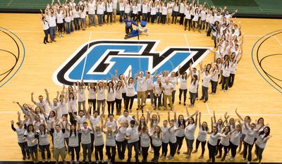 In this Sunday, April 6, 2014 photo released by Grand Valley State University, sets of twins pose for a group photo in the field house at Grand Valley State University in Allendale, Mich. The school says there are 101 sets of twins this year, and that 52 sets of currently enrolled twin students showed up. They were joined by 12 sets of twins who are alumni and even a few infant twins. (AP Photo/Grand Valley State University, Amanda Pitts)