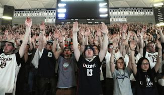 Connecticut students in Storrs, Conn., Monday April 7, 2014, raise their arms during a UConn free throw while they watch the broadcast of the UConn and Kentucky  men's basketball game for the NCAA title. (AP Photo/Jessica Hill)