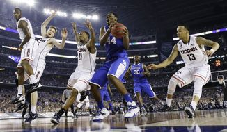 Kentucky center Dakari Johnson (44) grabs the ball between defenders Connecticut guard Ryan Boatright (11) and guard Shabazz Napier (13) during the second half of the NCAA Final Four tournament college basketball championship game Monday, April 7, 2014, in Arlington, Texas. (AP Photo/David J. Phillip)