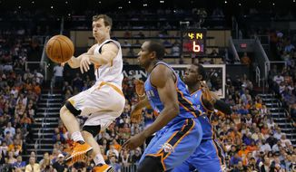 Phoenix Suns guard Goran Dragic (1), of Slovenia, dishes off as Oklahoma City Thunder forward Serge Ibaka, right, of Congo, defends, during the first half of an NBA basketball game on Sunday, April 6, 2014, in Phoenix. The Suns won 122-115. (AP Photo/Matt York)