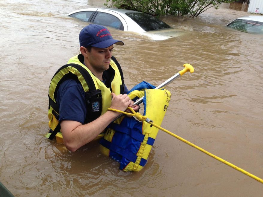 Firefighter Rusty Murphy wades through flood waters in a mobile home park in Pelham, Ala., on Monday, April 7, 2014. Police and firefighters rescued about a dozen people who were trapped by muddy, fast-moving water after storms dumped torrential rains in central Alabama. (AP Photo/Jay Reeves)