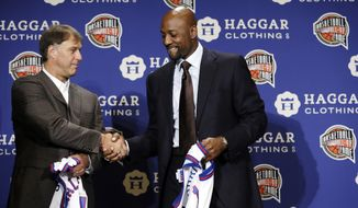 Former NBA player Sarunas Marciulionis, of Lithuania, greets former NBA player Alonzo Mourning, right, on stage during the Naismith Memorial Basketball Hall of Fame class of 2014 announcement, Monday, April 7, 2014, in Dallas. (AP Photo/Charlie Neibergall)