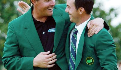 Phil Mickelson hugs last year's Masters winner Canada's Mike Weir after being presented his green jacket after winning the Masters championship with a nine-under-par at the Augusta National Golf Club in Augusta, Ga., Sunday, April 11, 2004.   (AP Photo/Dave Martin)