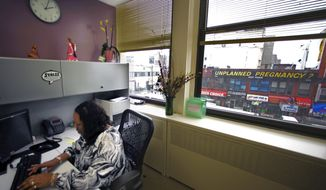 **FILE** Felicia Morris-Bolar, center director of Planned Parenthood in the Bronx borough of New York City, works in her office with a view from her window of the EMC Pregnancy Center signage on March 23, 2011. (Associated Press)