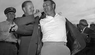 Arnold Palmer, right, slips into his green jacket with help from Jack Nicklaus after winning his fourth Masters golf championship on April 12, 1964. (AP Photo)