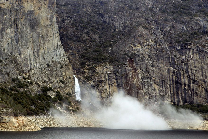 In this photo supplied by Yosemite National Park, dust rises from a rockfall on Monday, March 31, 2014. Officials at Yosemite National Park say a massive amount of rock has fallen from a cliff, closing a hiking trail. The National Park Service said nobody was hurt on March 31 when approximately 16,000 tons of rock fell 500 feet from a cliff near Hetch Hetchy Reservoir. Officials say the rock crashed down from a cliff east of Wapama Falls. Some 400 feet of the Rancheria Falls Trail were destroyed and park staff says it will remain closed for now. Park officials say hikers can still get to Wampama Falls starting at O'Shaughnessy Dam. (AP Photo/Yosemite National Park)