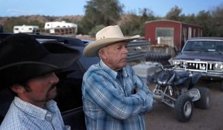 Cliven Bundy, right, and Clance Cox, left, stand at the Bundy ranch near Bunkerville Nev. Saturday, April 5, 2014. The U.S. Bureau of Land Management started taking cattle on Saturday from rancher Bundy, who it says has been trespassing on U.S. land without required grazing permits for over 25 years. Bundy doesn't recognize federal authority on land he insists belongs to Nevada. (AP Photo/Las Vegas Review-Journal, John Locher)