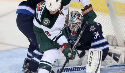 Winnipeg Jets' Adam Pardy (2) battles with Minnesota Wild's Cody McCormick (8) in front of Jets' goaltender Michael Hutchinson (34) during first period NHL hockey action in Winnipeg, Manitoba, Monday, April 7, 2014. (AP Photo/The Canadian Press, Trevor Hagan)