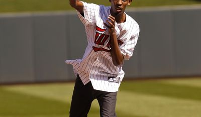 """Barkhad Abdi, who costarred in the movie """"Captain Phillips,"""" throws out the ceremonial pitch before the Minnesota Twins host the Oakland Athletics in a home opener MLB American League baseball game in Minneapolis, Monday, April 7, 2014.  (AP Photo/Ann Heisenfelt)"""