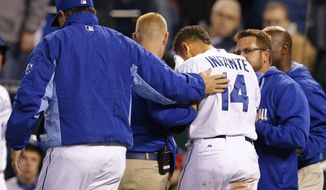 Kansas City Royals manager Ned Yost, left, comforts Omar Infante (14) as trainers help him from the field during the seventh inning of the MLB American League baseball game against the Tampa Bay Rays at Kauffman Stadium in Kansas City, Mo., Monday, April 7, 2014. Infante was hit by a pitch from Tampa Bay Rays relief pitcher Heath Bell. The Royals defeated the Rays 4-2. (AP Photo/Orlin Wagner)
