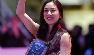 FILE - In this Jan. 9, 2014 file photo, Michelle Kwan waves as she holds a World Figure Skating Hall of Fame plaque during a ceremony at the U.S. Figure Skating Championships in Boston. Kwan has been honored Monday April 7, 2014,  by Figure Skating in Harlem for providing an inspiration to the hundreds of young girls who have been in the program. (AP Photo/Steven Senne, File)