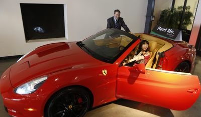 In this Wednesday, March, 26, 2014 photo, Adam Belsky, Enterprise Exotic Car Collection manager shows Jingyi Yang, 21, from Seattle a 2014 Ferrari California displayed for rent at the Enterprise Exotic Car Collection showroom near Los Angeles International Airport. (AP Photo/Damian Dovarganes)