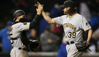 Pittsburgh Pirates catcher Russell Martin (55) and relief pitcher Jason Grilli (39) celebrate after defeating the Chicago Cubs in the MLB National League baseball game on Tuesday, April 8, 2014, in Chicago. The Pittsburgh Pirates won 7-6. (AP Photo/Andrew A. Nelles)
