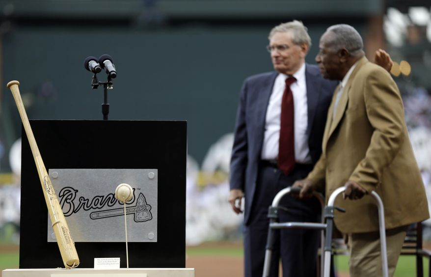 The bat and ball from Hank Aaron's 715th home run stand on display at left as Aaron, right, talks with Commissioner of Major League Baseball Bud Selig during a ceremony celebrating the 40th anniversary of the home run before the start of a baseball game between the Atlanta Braves and the New York Mets, Tuesday, April 8, 2014, in Atlanta. (AP Photo/David Goldman)