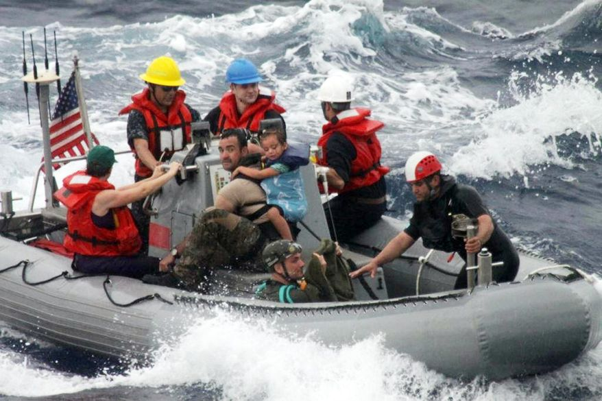 """FILE - In this April 6, 2014, file photo, provided by the U.S. Coast Guard, sailors from the frigate USS Vandegrift assist in the rescue of the Kaufman family with a sick infant on the ship's small boat, as part of a joint U.S. Navy, Coast Guard and California Air National Guard rescue effort. None of the three federal agencies that helped rescue the ill 1-year-old, Lyra Kaufman, and her family from their broken down sailboat about 900 miles off Mexico's Pacific coast plan to seek reimbursement for the cost of the operation. Officials from the Navy, Coast Guard and California Air National Guard said Tuesday, April 8, 2014, they don't charge for search-and-rescue missions. """"We don't want people in trouble at sea to hesitate to call for help for fear they'll be charged for assistance,"""" said Lt. Anna Dixon of the 11th Coast Guard District, which oversaw the operation but did not send vessels or aircraft to the stranded sailboat. She said that helping at sea is a time-honored tradition and a requirement of international maritime convention. The Navy warship that picked up the family on Sunday is expected to reach San Diego on Wednesday. (AP Photo/U.S. Coast Guard, File)"""