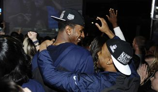 Connecticut men's basketball players DeAndre Daniels, left, and Tor Watts celebrate as they watch television coverage of the final seconds the UConn women's team's 79-58 win over Notre Dame in the NCAA women's college basketball tournament title game, Tuesday, April 8, 2014, in Storrs, Conn. (AP Photo/Jessica Hill)