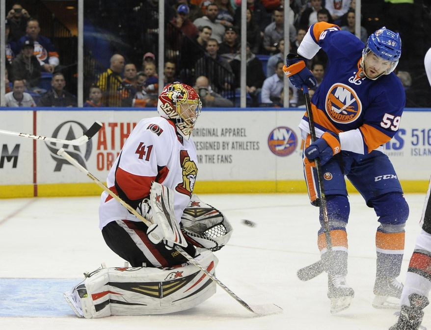 Ottawa Senators goalie Craig Anderson (41) blocks a shot on goal by New York Islanders' Brett Gallant (59) in the second period of an NHL hockey game Tuesday, April 8, 2014, in Uniondale, N.Y. (AP Photo/Kathy Kmonicek)
