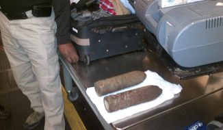 This Monday, April 7, 2014 photo provided by the Transportation Security Administration (TSA) shows two World War I artillery shells discovered by baggage screeners in checked luggage that arrived on a flight from London at Chicago's O'Hare International Airport. The TSA says the bags belonged to a 16-year-old and a 17-year-old who were returning from a school field trip to Europe. A bomb disposal crew determined the shells were inert and no one was ever in danger. The teens were questioned then allowed to travel onward. They weren't charged. (AP Photo/Transportation Security Administration)