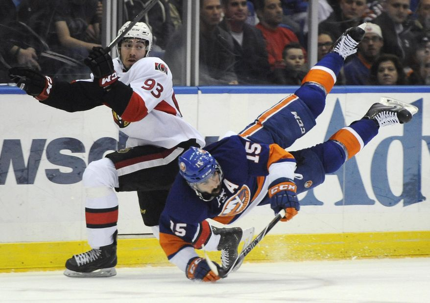 Ottawa Senators' Mika Zibanejad (93) collides with New York Islanders' Cal Clutterbuck (15) during the first period of an NHL hockey game Tuesday, April 8, 2014, in Uniondale, N.Y. (AP Photo/Kathy Kmonicek)