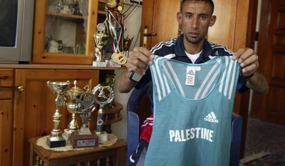 FILE - In this Friday, April 4, 2008 file photo, Palestinian athlete Nader Masri, 28, holds the shirt he will be wearing when competing in the 2008 Olympics, at his home in Beit Hanoun, northern Gaza Strip. On Tuesday, April 8, 2014 Israel's high court has upheld a decision by the military to prevent Nader Masri, 34, a Gaza Olympian, from leaving the coastal strip to participate in a marathon in the West Bank. Israel has severely restricted the movement of people and goods in and out of Gaza since the Islamic militant Hamas took control there in 2007. Tuesday's ruling ends hopes of 34-year-old Nader Masri to participate in Friday's marathon in biblical Bethlehem. Israel says only humanitarian hardship cases are allowed to leave Gaza. (AP Photo/Majed Hamdan)