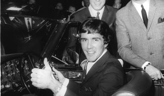 """FILE--In this Oct. 19, 1965 file photo, Dave Clark, gives a thumb's up sitting in a Bentley Continental, with the other members of the band """"Dave Clark Five Beat Group,"""" Dennis Payton, left, and Mike Smith, at the International Motor Show at Earl's Court, in London. There was more to the 1960s British invasion than the Beatles, as any fan of """"Catch Us If You Can"""" or """"Because"""" or - get ready to shimmy - """"Glad All Over."""" The hit tunes were among those recorded by the influential U.K. band that gets its due in """"The Dave Clark Five and Beyond: Glad All Over,"""" a PBS documentary airing Tuesday, April 8, 2014 (check local listings).  (AP Photo, file)"""