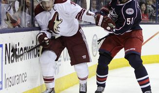 Phoenix Coyotes' Shane Doan, left, and Columbus Blue Jackets' Fedor Tyutin, of Russia, fight for a loose puck during the first period of an NHL hockey game Tuesday, April 8, 2014, in Columbus, Ohio. (AP Photo/Jay LaPrete)