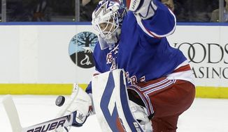 New York Rangers goalie Henrik Lundqvist, of Sweden, stops a shot on the goal from Carolina Hurricanes' Alexander Semin during the first period of an NHL hockey game Tuesday, April 8, 2014, in New York. (AP Photo/Frank Franklin II)