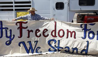 """John Banks holds up a banner during a rally in support of Cliven Bundy near Bunkerville Nev. Monday, April 7, 2014, 2014. The Bureau of Land Management has begun to round up what they call """"trespass cattle"""" that rancher Cliven Bundy has been grazing in the Gold Butte area 80 miles northeast of Las Vegas.  (AP Photo/Las Vegas Review-Journal, John Locher)"""