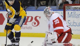 Buffalo Sabres left winger Nicolas Deslauriers (44) deflects the puck on Detroit Red Wings goaltender Jimmy Howard (35) during the first period of an NHL hockey game in Buffalo, N.Y., Tuesday, April 8, 2014. (AP Photo/Gary Wiepert)