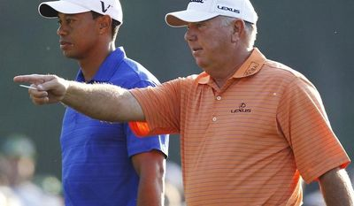 Tiger Woods, left, walks to the 12th tee with Mark O'Meara during a practice round for the Masters golf tournament Monday, April 2, 2012, in Augusta, Ga. (AP Photo/Chris O'Meara)