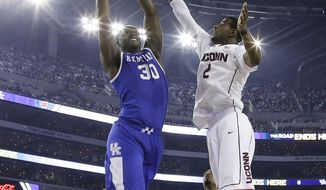 Kentucky forward Julius Randle, left, drives to the basket past Connecticut forward DeAndre Daniels (2) during the second half of the NCAA Final Four tournament college basketball championship game Monday, April 7, 2014, in Arlington, Texas. (AP Photo/David J. Phillip)