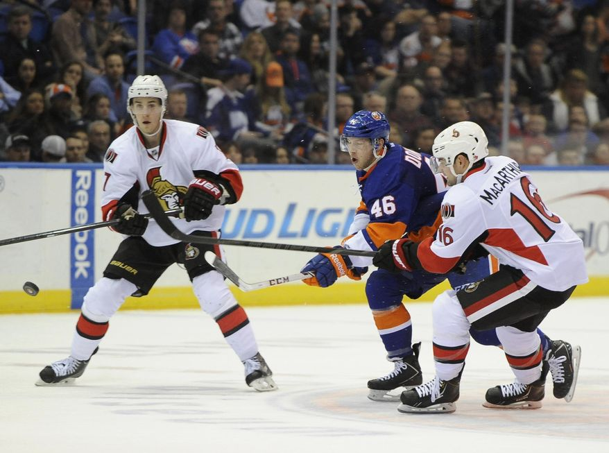 New York Islanders' Matt Donovan (46) and Ottawa Senators' Kyle Turris (7) and Clarke MacArthur (16) vie for the puck during the second period of an NHL hockey game Tuesday, April 8, 2014, in Uniondale, N.Y. (AP Photo/Kathy Kmonicek)