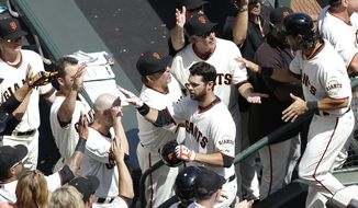 San Francisco Giants' Brandon Belt, center, is congratulated after hitting a two-run home run off of Arizona Diamondbacks pitcher Trevor Cahill that scored Angel Pagan, right, during the first inning of the home opener MLB National League baseball game in San Francisco, Tuesday, April 8, 2014. (AP Photo/Jeff Chiu)