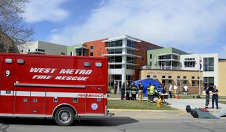 In this Monday, April 7, 2014 photo, crews work to shower and disrobe students and faculty during an evacuation after people were exposed to hazardous skin irritants at Jefferson County Open School, in Lakewood, Colo. Seven students at the suburban Denver school were hospitalized and about two dozen others and a teachers' aide were decontaminated on site after complaining of skin and eye irritation. (AP Photo/The Denver Post, AAron Ontiveroz) MAGS OUT; TV OUT; INTERNET OUT; NO SALES; NEW YORK POST OUT; NEW YORK DAILY NEWS OUT
